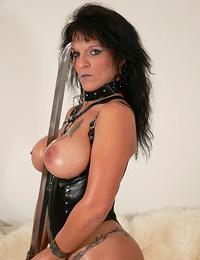 Mature dominatrix rubing her pussy with a samurai sword